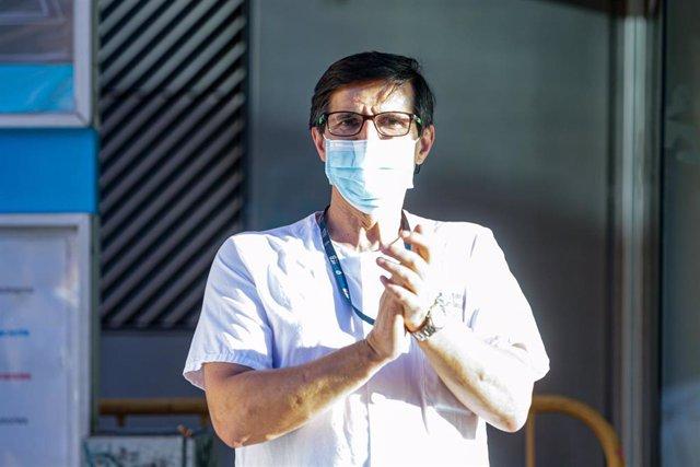 Un sanitario del Hospital General Universitario Gregorio Marañón y un transeúnte aplauden a las puertas del hospital tras la convocatoria a través de las redes sociales de un último aplauso en homenaje a los profesionales sanitarios y demás sectores que h