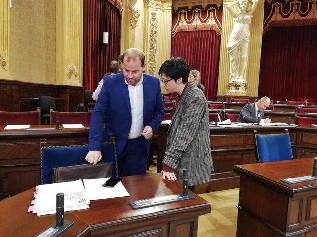 El conseller Miquel Mir conversa con la portavoz socialista, Sílvia Cano, en el Parlament.