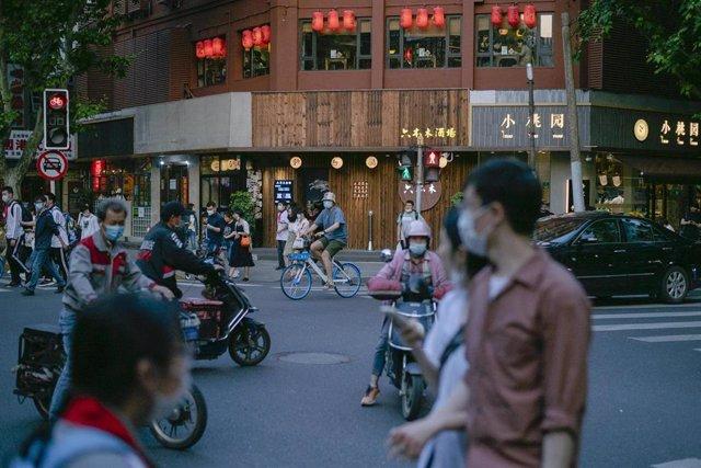 Varias personas con mascarillas en las calles de Shanghái por el coronavirus.