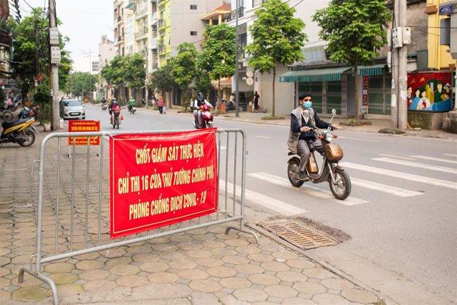 Un hombre con mascarilla circula en moto por las calles de Hanói