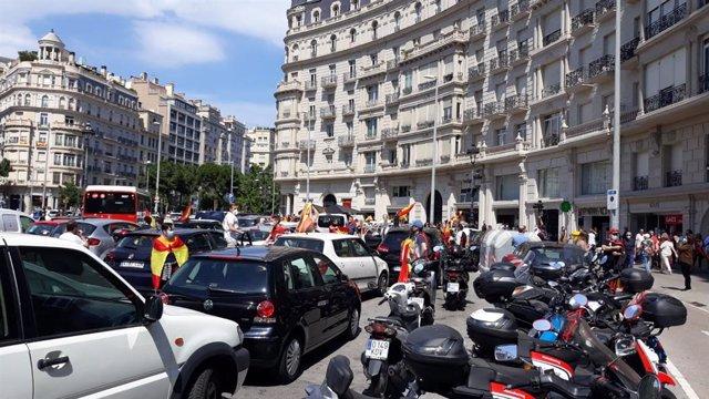 Persones i cotxes concentrats a la plaça Francesc Macià de Barcelona per la manifestació amb cotxe de Vox