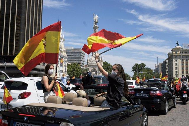 Coches y motos, con pancartas y banderas de España, circulan por las calles de la capital en la manifestación de Vox