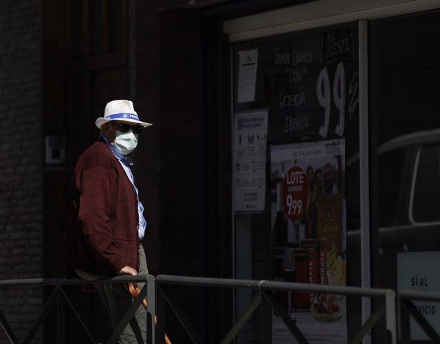 Un hombre camina con mascarilla