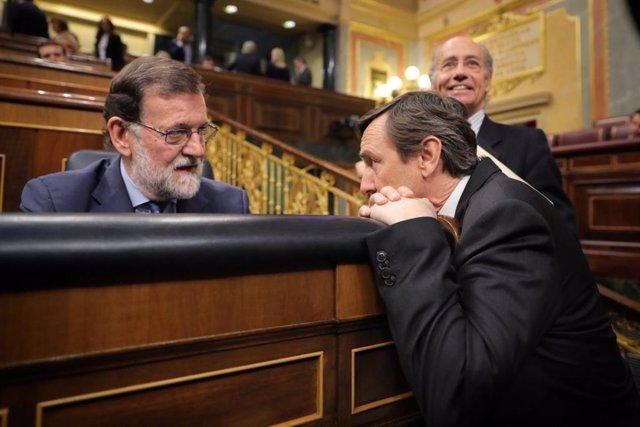 El que fuera presidente del Gobierno, Mariano Rajoy, conversa en el  escaño con Rafael Hernando, entonces portavoz del Grupo Popular en el Congreso.