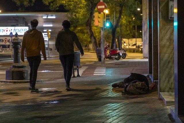 Una persona sense llar dormint al carrer, prop de l'Estació de Sants de Barcelona, durant la nit del recompte de persones sense sostre organitzada per la Fundació Arrels el passat 14 de maig del 2020, durant l'epidèmia del coronavirus.