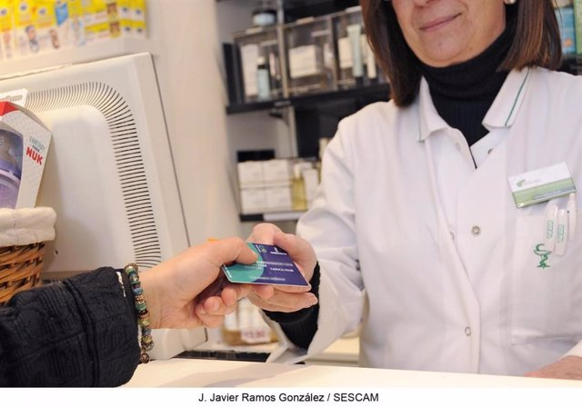 Una farmacéutica recogiendo una tarjeta sanitaria