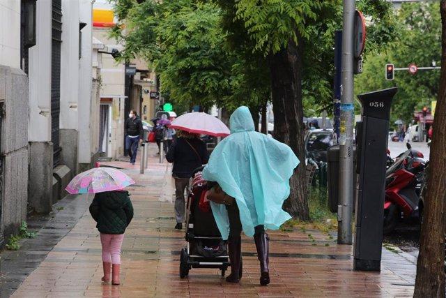 Una mujer y una niña pasean con paraguas en Madrid en un día de lluvia y bajada de temperaturas
