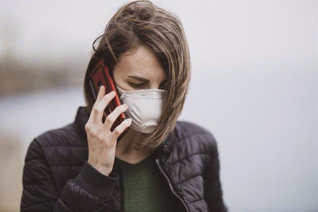 Mujer con mascarilla hablando por teléfono.