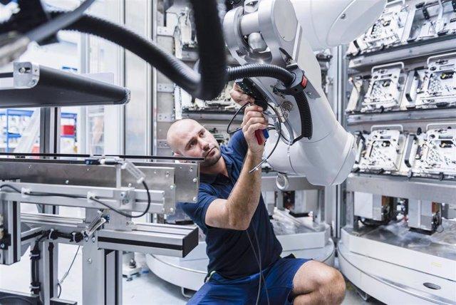 Hombre trabajando con robot industrial en una fábrica moderna