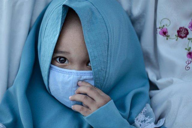 Una niña con mascarilla en Indonesia