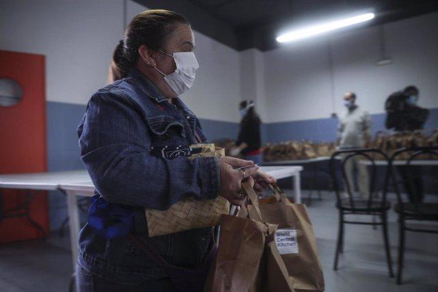 Una mujer recibe alimentos del Proyecto Fraternitas, que atiende a familias vulnerables de dos de los barrios más pobres de España.