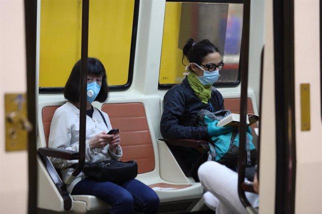 Varios pasajeros viajan dentro de un tren de Metro de Madrid, el mismo día de la presentación de una cámara térmica con la que se controlará la temperatura de los trabajadores del Puesto de Mando de Metro en el Puesto de Mando de la estación de Metro Alto