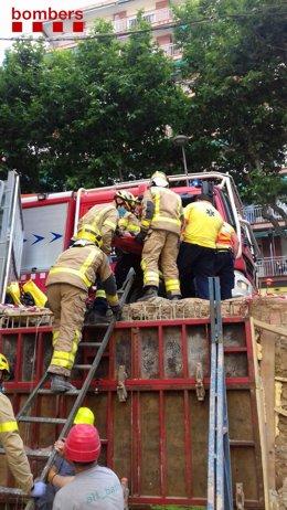 Efectius de Bombers de la Generalitat rescaten un treballador atrapat després de bolcar un carretó elevador a Molins de Rei (Barcelona).