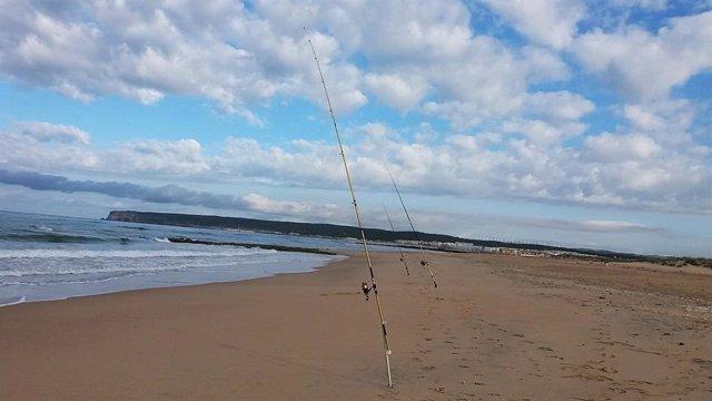Cañas de pescar en la orilla de una playa de Cádiz. Imagen de archivo.