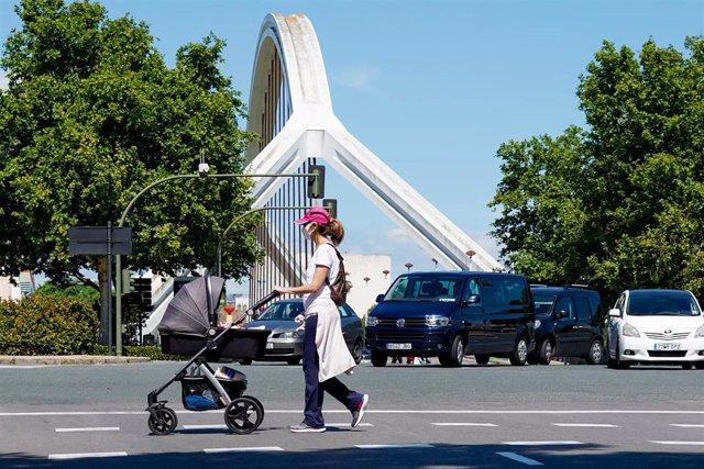 Una madre pasea a su hijo con el puente de la Barqueta detrás,  un día después de que el Gobierno de España anunciara las medidas de desescalada por la pandemia del coronavirus, (Covid-19). En Sevilla (Andalucía, España), a 29 de abril de 2020.