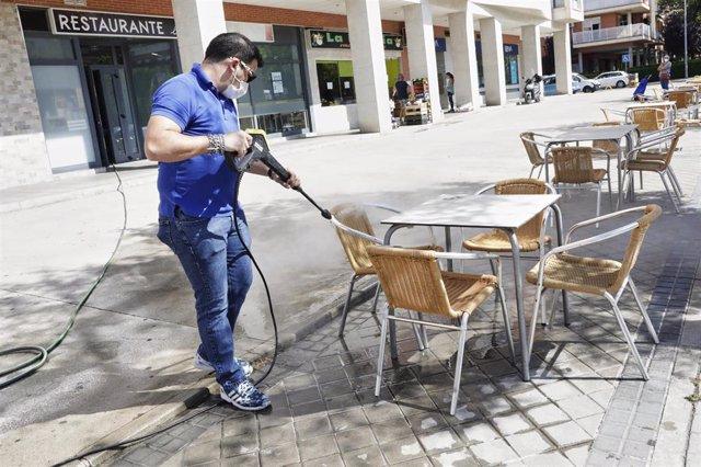 Un trabajador desinfecta la terraza de un restaurante antes de reabrir sus puertas