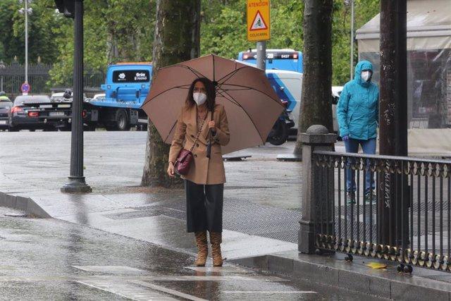 Una mujer con paraguas en Madrid en un día de lluvia y bajada de temperaturas en toda España, en que en gran parte de la Península y Baleares se espera nubosidad, con chubascos y tormentas casi generalizados, que podrán ser localmente fuertes o persistent