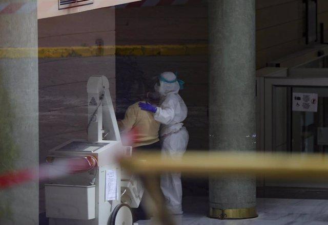 Personal sanitario ayuda a una anciana en el interior del Hotel Alcorá tras ser adaptado como hospital para recibir pacientes con coronavirus. En Sevilla, (Andalucía, España), a 30 de enero de 2020.