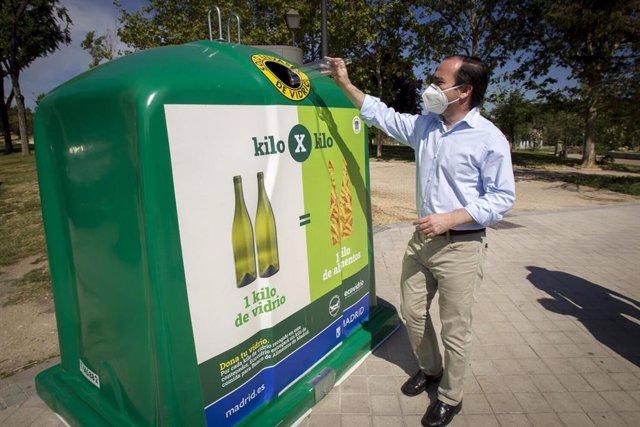 El delegado de Medio Ambiente y Movilidad, Borja Carabante, depositando un vidrio en uno de los contenedores situado en las inmediaciones de la boca de metro de Laguna