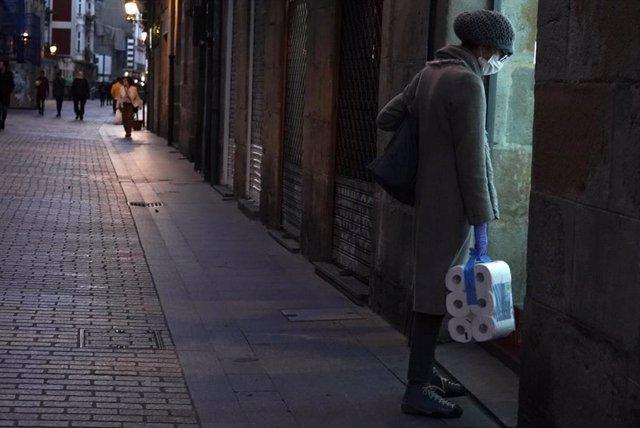 Una mujer protegida con mascarilla y con un paquete de papel higiénico en la mano pasea por Bilbao tras la declaración de Estado de Alarma en todo el país por el avance del coronavirus, en Bilbao, Vizcaya, País Vasco (España).