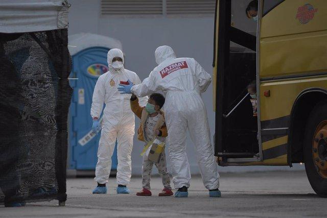 Trabajadores con trajes de protección ayudan a un niño en un minubús en Malasia