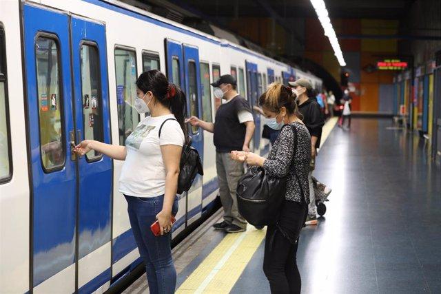 Varios pasajeros abren la puerta de un tren de Metro de Madrid.
