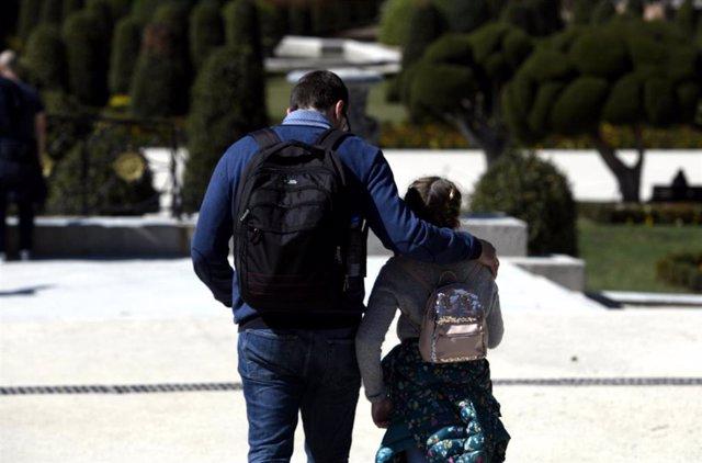 Un padre junto a su hija pasean por el Parque del Retiro en el primer día sin colegio por el riesgo del coronavirus, en Madrid (España) a 11 de marzo de 2020.