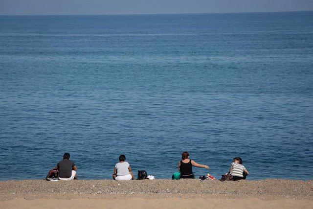 Varias personas sentadas en la Playa de la Barceloneta, en Barcelona.