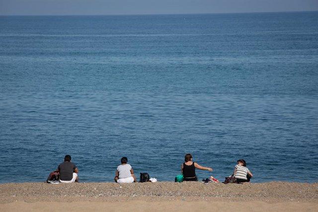 Diverses persones assegudes a la Platja de la Barceloneta, a Barcelona.