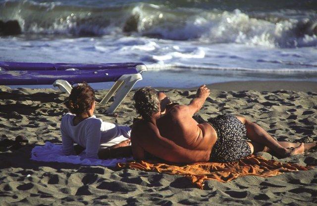 Dos turistes a la platja en una imatge d'arxiu