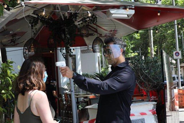 Un camarero mide la temperatura de sus clientes en una céntrica terraza madrileña