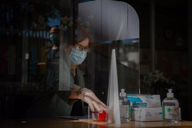 Una mujer atiende en el Institut Escola Coves d'en Cimany, ubicado en el barrio El Carmel de Barcelona, durante el primer día de atención presencial para la preinscripción escolar del curso 2020/2021, en Barcelona