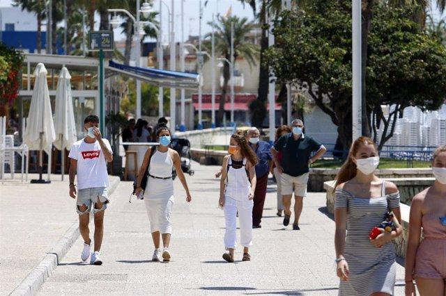 Un grupo de personas pasean por el paseo marítimo de Pedregalejo  durante la Fase 1 en Málaga a 20 de mayo del 2020