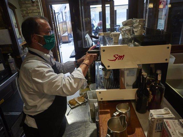Un camarero en la barra de un bar el día en el que se reabren al público los establecimientos de hostelería y restauración para consumo en el local.