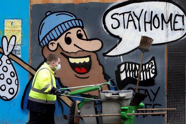 """Un hombre con mascarilla junto a un mural pintado con el lema """"Stay home!"""", """"¡Quédate en casa!"""""""