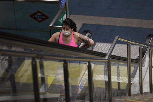 Una mujer protegida con mascarilla hace uso del Metro de Madrid