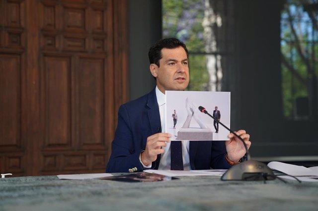 El presidente de la Junta de Andalucía, Juanma Moreno, muestra un boceto de escultura de homenaje a profesionales esenciales de la crisis del coronavirus, en el transcurso de una videoconferencia con alcaldes de las capitales de la comunidad.