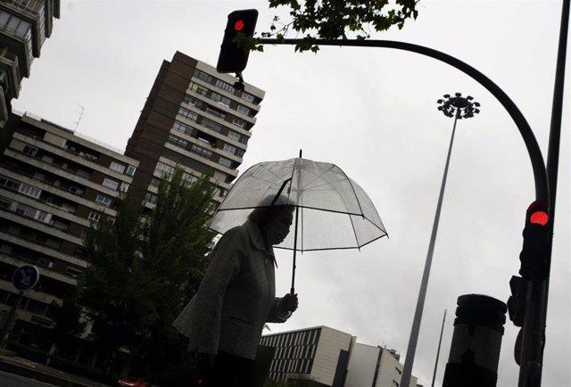 Una mujer pasea con un paraguas en la capital en un día de lluvia y bajada de temperaturas en toda España.