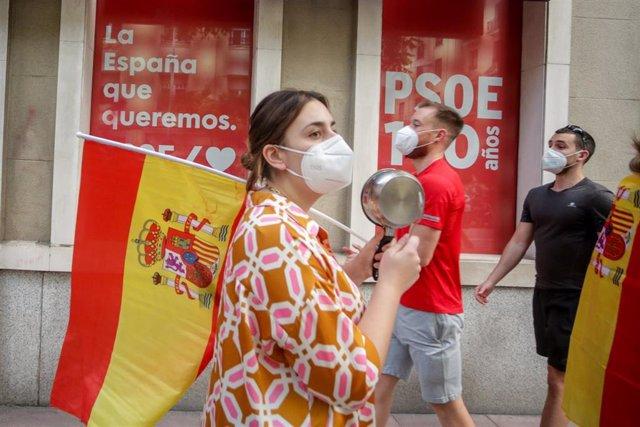 Una mujer toca una cacerola durante el cuarto día de protestas por la gestión del Gobierno en la crisis del coronavirus, frente a la sede del PSOE de la calle Ferraz en Madrid a 19 de mayo de 2020.