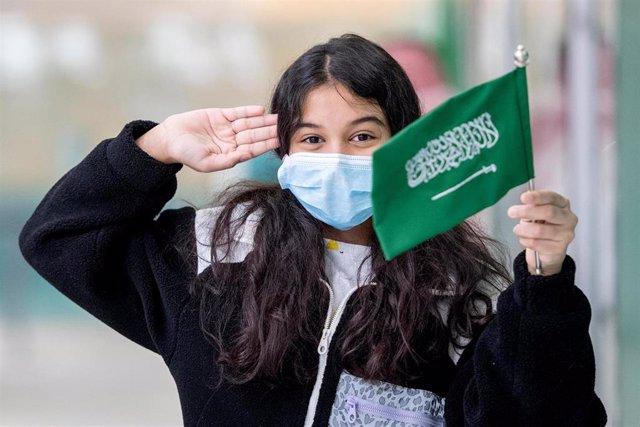 Una muchacha saudí sostiene una bandera de su país.