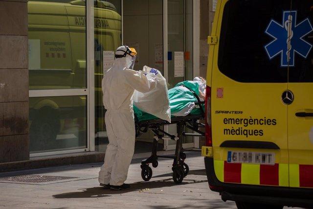 Un sanitari protegit amb un vestit transporta a una persona contagiada amb coronavirus a Barcelona.