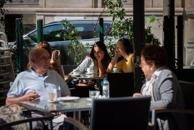 Diverses persones gaudeixen en una terrassa d'un bar durant el primer dia de la Fase 1. A Barcelona, Catalunya (Espanya), a 25 de maig de 2020.