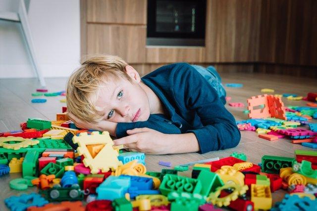Niño triste, estrés y depresión, agotamiento con juguetes esparcidos alrededor.