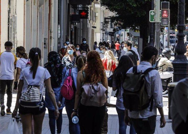 Varias personas caminan por una calle del centro de Valencia después de que el Ministerio de Sanidad autorizara a que la totalidad de la Comunidad Valenciana pasase en su conjunto a la fase 1 de la desescalada (archivo)