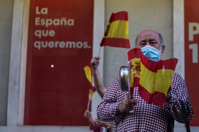 Un hombre mayor golpea una cacerola en señal de protesta, en la sede del PSOE.