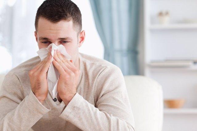 Un hombre estornuda y se tapa con un pañuelo