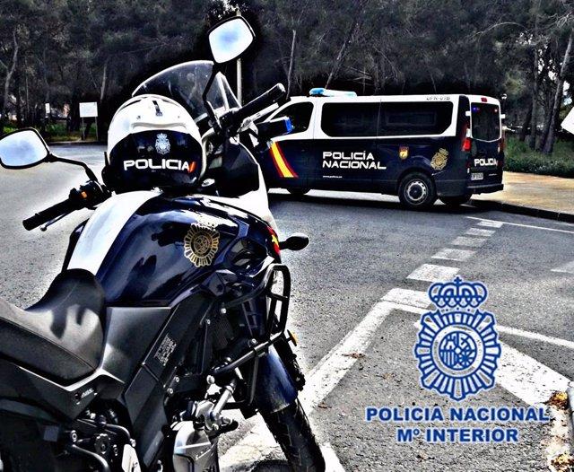 Imagen de una moto y un furgón de Policía Nacional