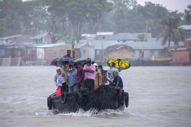Una embarcación con pasajeros cruzando un río en Bangladesh horas antes de la llegada del ciclón 'Amphan'