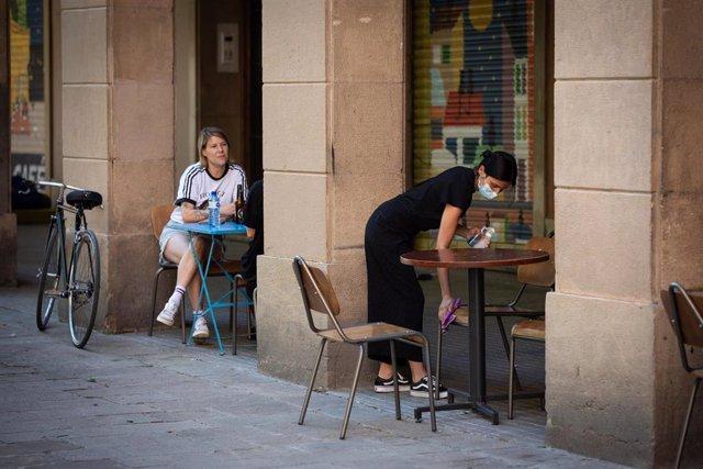 Una camarera limpia varias sillas y una mesa de la terraza de un bar durante el segundo día de la reapertura al público de las terrazas al aire libre, durante el segundo día de la Fase 1 en Barcelona, Catalunya (España) a 26 de mayo de 2020.