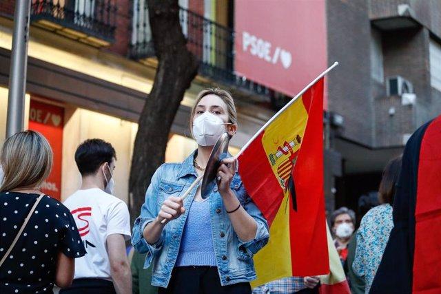 Una mujer con mascarilla sostiene una bandera de España mientras golpea una cacerola en señal de protesta durante la manifestación celebrada en la puerta de la sede del PSOE de la calle Ferraz de Madrid.
